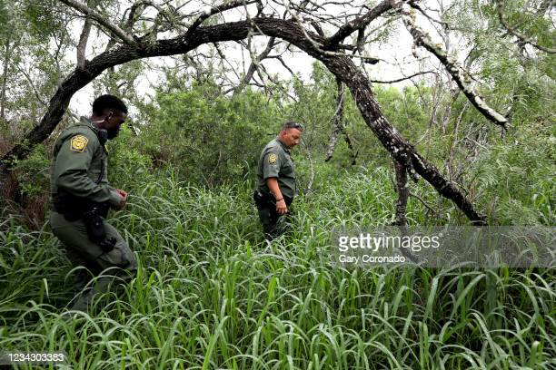 Border Patrol agents Ebenezar Oyenola, left, and Jaime Cavazos, Rio Grande Valley Sector, look for the remains of a deceased male migrant, Alfonso...