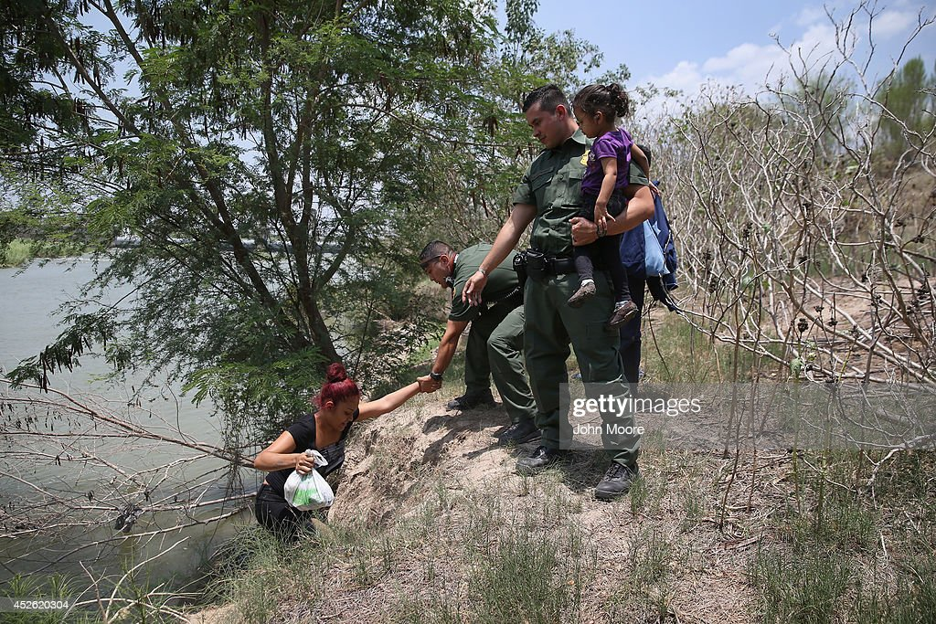 U.S. Border Patrol agents help a mother and child from El Salvador after they crossed the Rio Grande illegally into the United States on July 24, 2014 in Mission, Texas. Tens of thousands of immigrant families and unaccompanied minors have crossed illegally into the United States this year and presented themselves to federal agents, causing a humanitarian crisis on the U.S.-Mexico border.