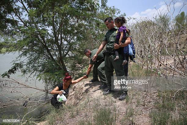 S Border Patrol agents help a mother and child from El Salvador after they crossed the Rio Grande illegally into the United States on July 24 2014 in...