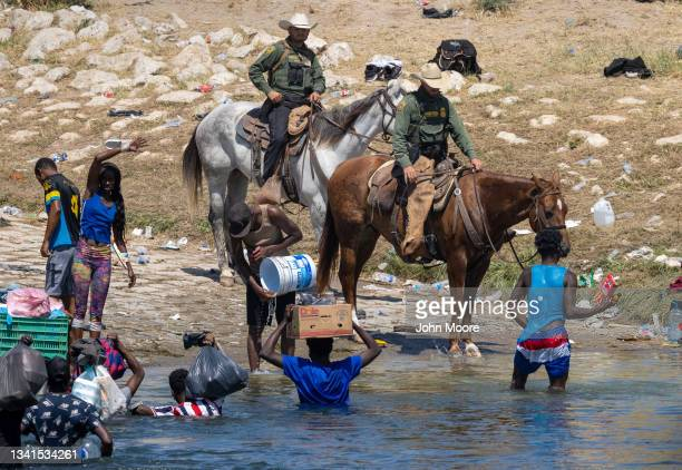 Border Patrol agents interact with Haitian immigrants on the bank of the Rio Grande in Del Rio, Texas on September 20, 2021 as seen from Ciudad...