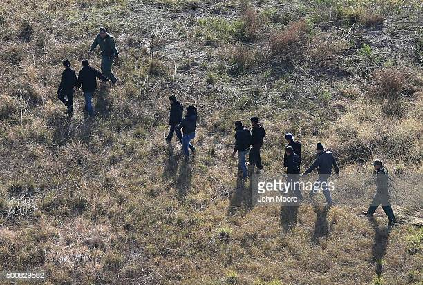Border Patrol agents lead undocumented immigrants out the brush after capturing them near the U.S.-Mexico border on December 10, 2015 at La Grulla,...