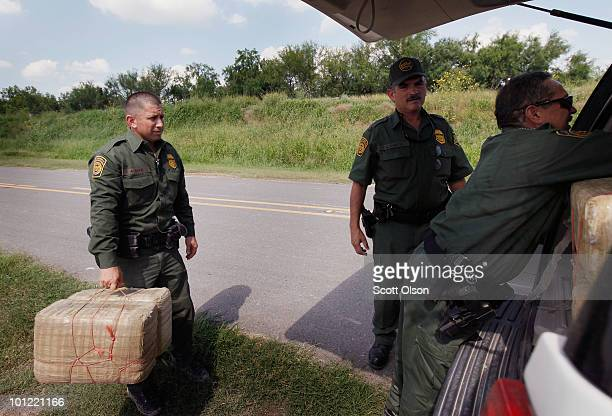 Border Patrol agents load bales of marijuana into their SUV after it was seized from a smuggler near the Mexican border on May 27 2010 near McAllen...