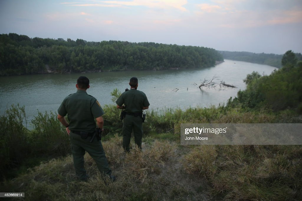 U.S. Border Patrol agents look for immigrants crossing the Rio Grande from Mexico (L), to the United States at dusk on July 24, 2014 near Mission, Texas. Tens of thousands of undocumented immigrants, many of them families or unaccompanied minors, have crossed illegally into the United States this year and presented themselves to federal agents, causing a humanitarian crisis on the U.S.-Mexico border. Texas' Rio Grande Valley has become the epicenter of the latest immigrant crisis, as more immigrants, especially Central Americans, cross illegally from Mexico into that sector than any other stretch of the America's 1,933 mile border with Mexico.