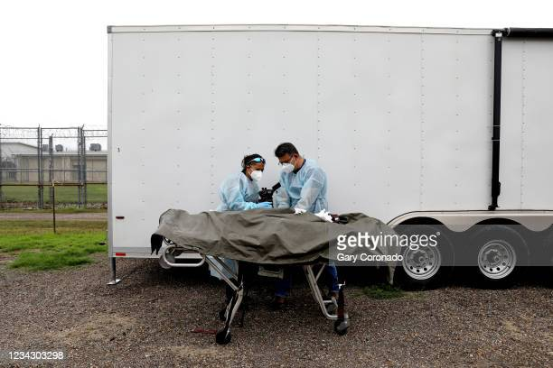 Border Patrol agents Nancy Balo, left, and Jerry Passement, take detail photographs of the finger prints of the remains of deceased female migrant,...