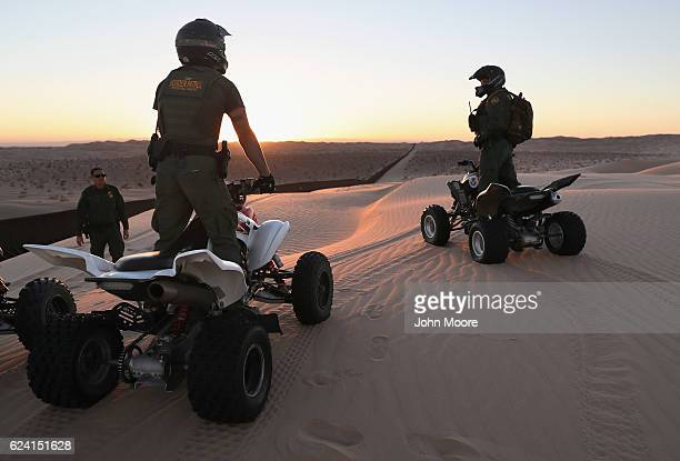 S Border Patrol agents on ATVs monitor the USMexico border fence at the Imperial Sand Dunes on November 17 2016 near Felicity California The 15foot...