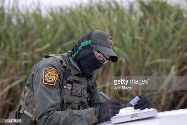 Border Patrol agents processes undocumented immigrants who were caught in a sugar cane field near a section of privately-built border wall under...
