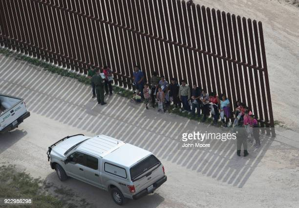 S Border Patrol agents question undocumented immigrant families at the USMexico border fence while taking them into custody on February 21 2018 near...