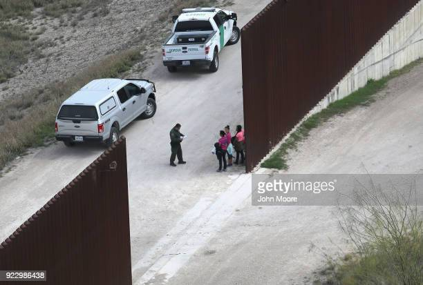 S Border Patrol agents question undocumented immigrant families at the USMexico border fence before transporting them to a US Border Patrol...