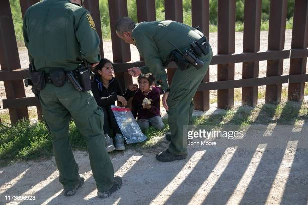 Border Patrol agents speak with a mother and daughter from Ecuador next to the border fence after detaining them on September 10, 2019 in Penitas,...