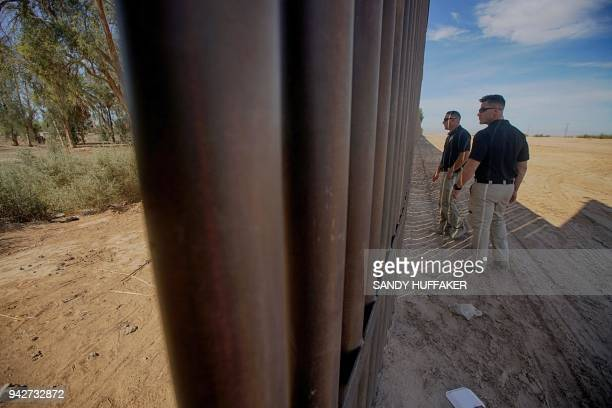 TOPSHOT Border Patrol agents stand along the border fence on April 6 2018 in Calexico California US President Donald Trump on April 5 2018 said he...