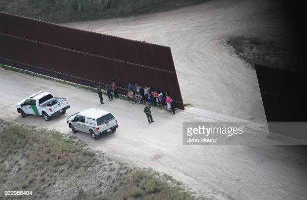 S Border Patrol agents stand with undocumented immigrant families at the USMexico border fence before transporting them to a US Border Patrol...