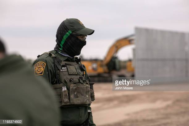 Border Patrol agents stands near a section of privately-built border wall under construction on December 11, 2019 near Mission, Texas. The hardline...