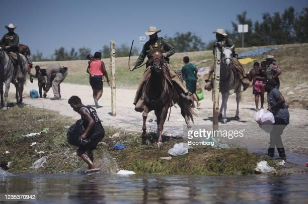 Border Patrol agents stop migrants crossing the Rio Grande River near the Del Rio-Acuna Port of Entry in Del Rio, Texas, U.S., on Sunday, Sept. 19,...