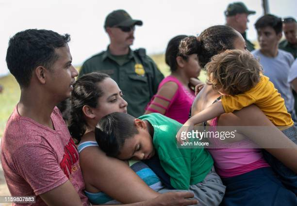 S Border Patrol agents supervise as Salvadorian immigrants wait to be transferred to the McAllen Border Patrol facility on July 02 2019 in Los Ebanos...