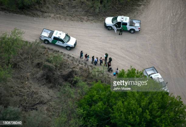 Border Patrol agents take asylum seekers into custody as seen from a Texas Department of Public Safety helicopter near the U.S.-Mexico Border on...