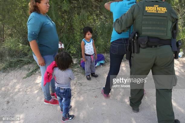 Border Patrol agents take Central American asylum seekers into custody on June 12, 2018 near McAllen, Texas. The immigrant families were then sent to...