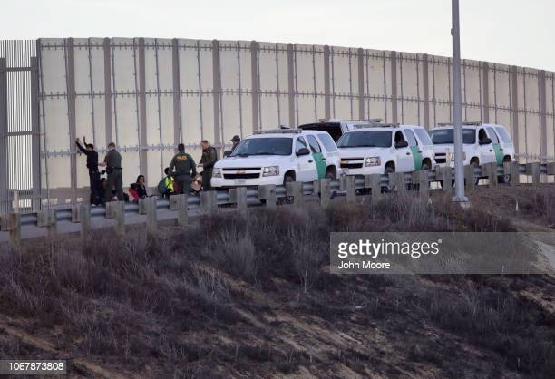 Border Patrol agents take immigrants into custody after they climbed over the main U.S.-Mexico border fence on December 2, 2018 from Tijuana, Mexico....