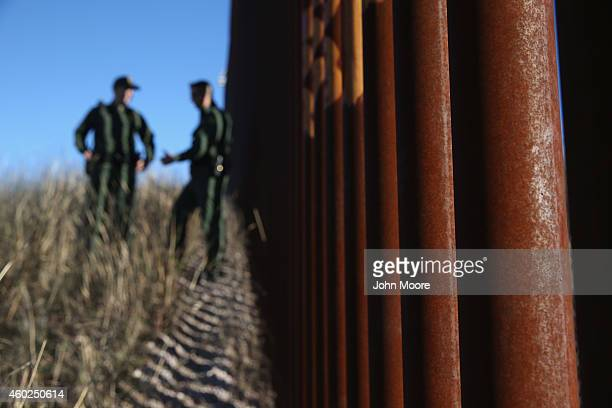 S Border Patrol agents talk next to the USMexico border fence on December 9 2014 near Nogales Arizona With increased manpower and funding in recent...