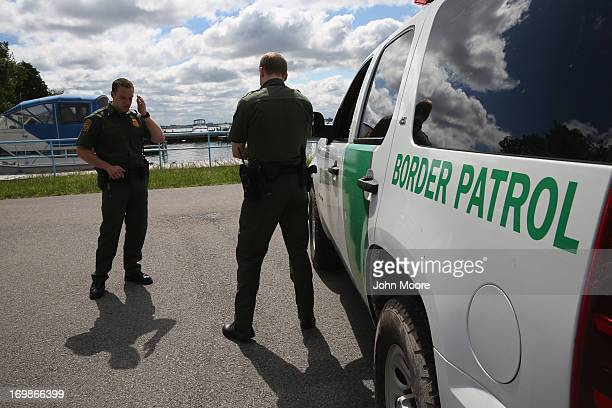S Border Patrol agents talk while at a marina on the Niagara River at the USCanada border on June 3 2013 in Beaver Island State Park New York US...