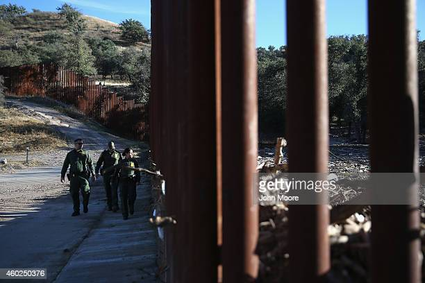 S Border Patrol agents walk along the USMexico border fence on December 9 2014 near Nogales Arizona With increased manpower and funding in recent...