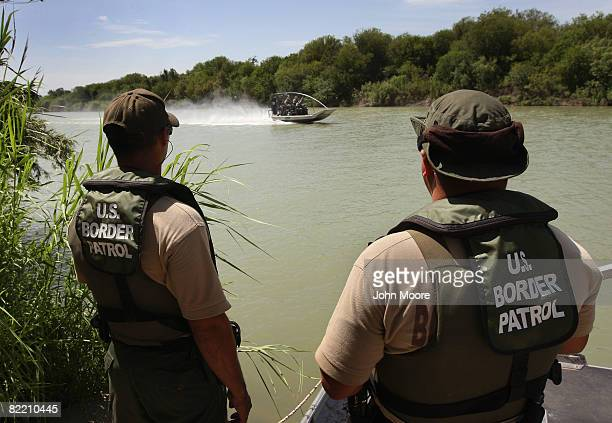 S Border Patrol agents watch colleagues motor past while patrolling for illegal immigrants in the Rio Grande River crossing into the United States...