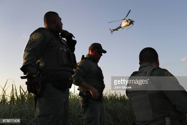 S Border Patrol agents watch over a group of undocumented immigrants after chasing them through a cane field near the USMexico Border on June 12 2018...
