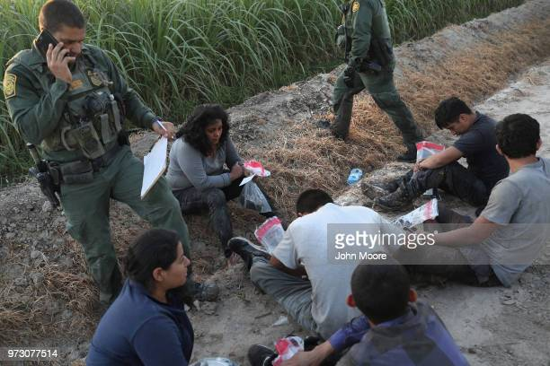 S Border Patrol agents watch over a group of undocumented immigrants after chasing and apprehending them in a cane field near the USMexico Border on...