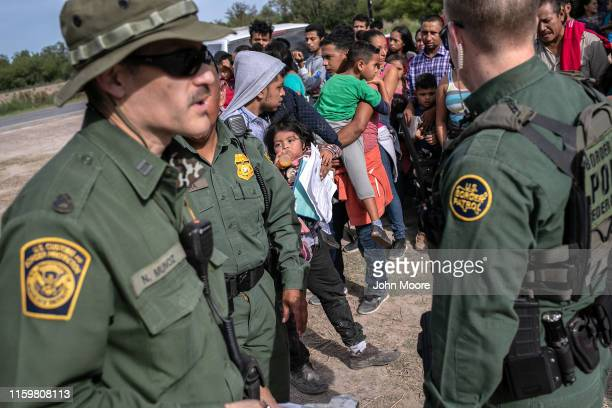 Border Patrol agents watch over immigrants after taking them into custody on July 02, 2019 in Los Ebanos, Texas. Hundreds of immigrants, most from...