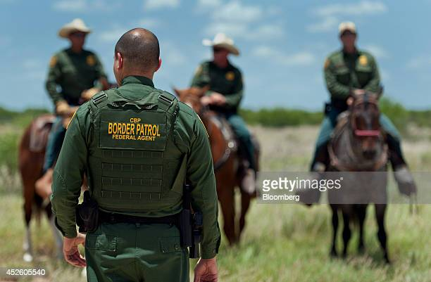 US Border Patrol agents work in a field near Carrizzo Springs Texas US on Thursday July 3 2014 The Border Patrol finds an average of one corpse a day...