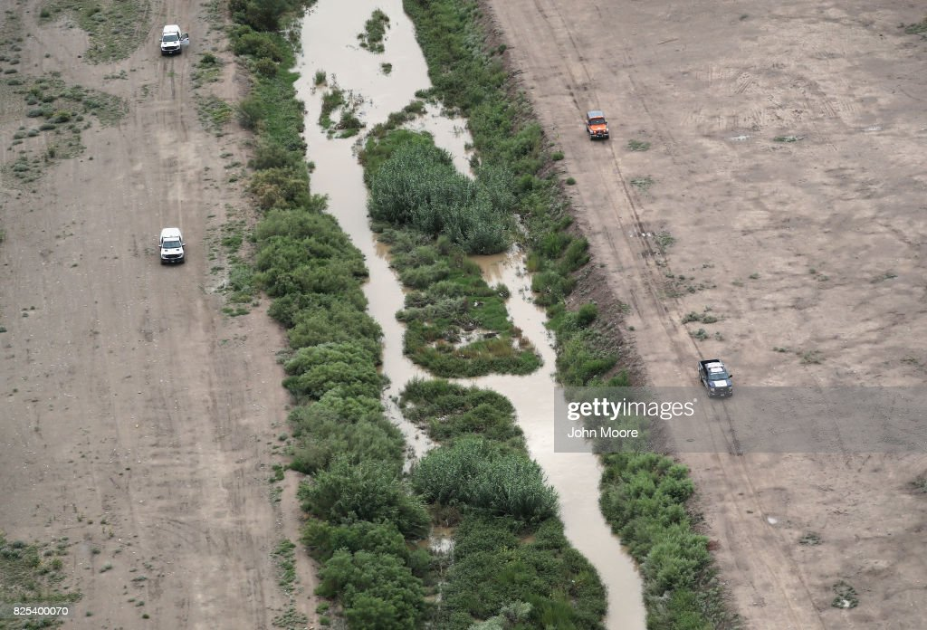 U.S. Border Patrol (L), and Mexican immigration agents perform a joint patrol along the Rio Grande at the U.S.-Mexico border as seen from a U.S. Customs and Border Protection helicopter on August 1, 2017 in El Paso, Texas. Logistical challenges are just some of the complications facing the construction of a border wall proposed by President Trump.