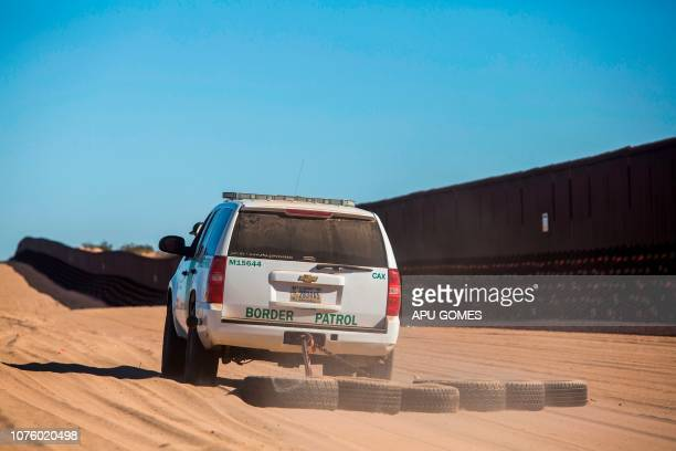 A Border Patrol car drags tires in the sand to make it easier to look for foot prints next to the USMexico border fence in the Yuha desert near...