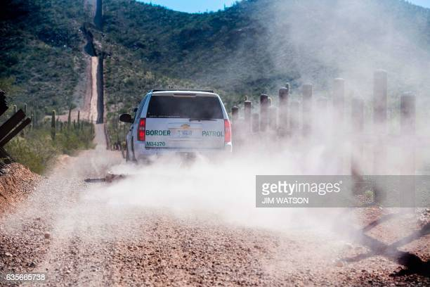 US Border Patrol drags tires to clear the road way of tracks as they guard the US/Mexico border near Lukeville Arizona on February 16 2017 This image...
