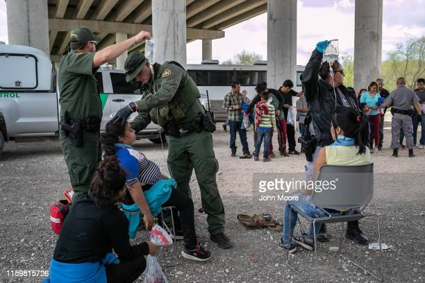 S Border Patrol medic treats an immigrant for heat exhaustion after taking her into custody on July 02 2019 in McAllen Texas The immigrants mostly...