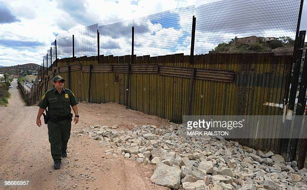 Border Patrol officer keeps watch over the border fence that divides the US from Mexico in the town of Nogales Arizona on April 23 2010 Two...