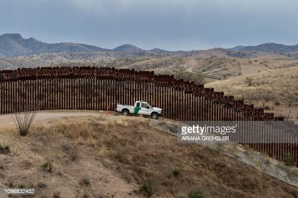 Border Patrol officer sits inside his car as he guards the US/Mexico border fence in Nogales Arizona on February 9 2019