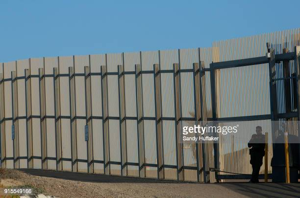 A border patrol officer stands guard along the USMexico border February 7 2018 in San Ysidro California A rally coinciding with the eve of Congress's...