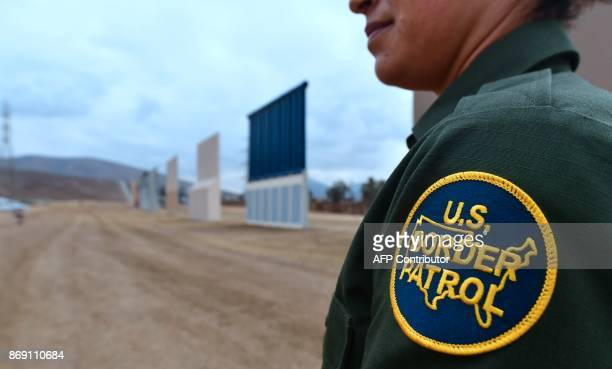 US Border Patrol officer Tekae Michael stands near prototypes of US President Donald Trump's proposed border wall on November 1 2017 in San Diego...