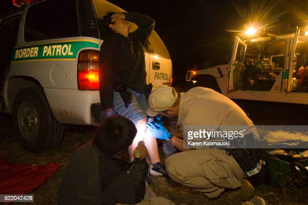 Border patrol officer treating injured illegal immigrant in Texas