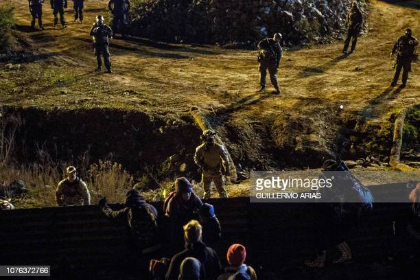 US border patrol officers deploy near the USMexico border fence to deter Central American migrants from crossing from Tijuana to San Diego as seen...