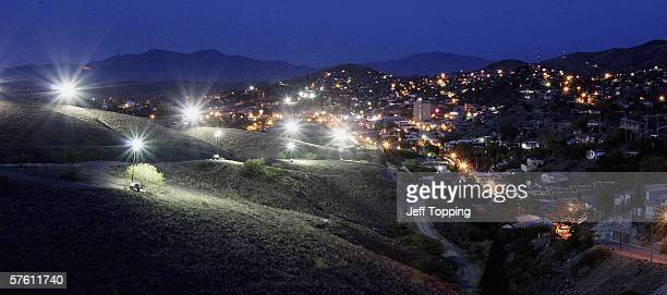 Border Patrol search lights glow from the hillside in the direction of Nogales, Sonora, Mexico where a wall separates the two cities along the U.S....