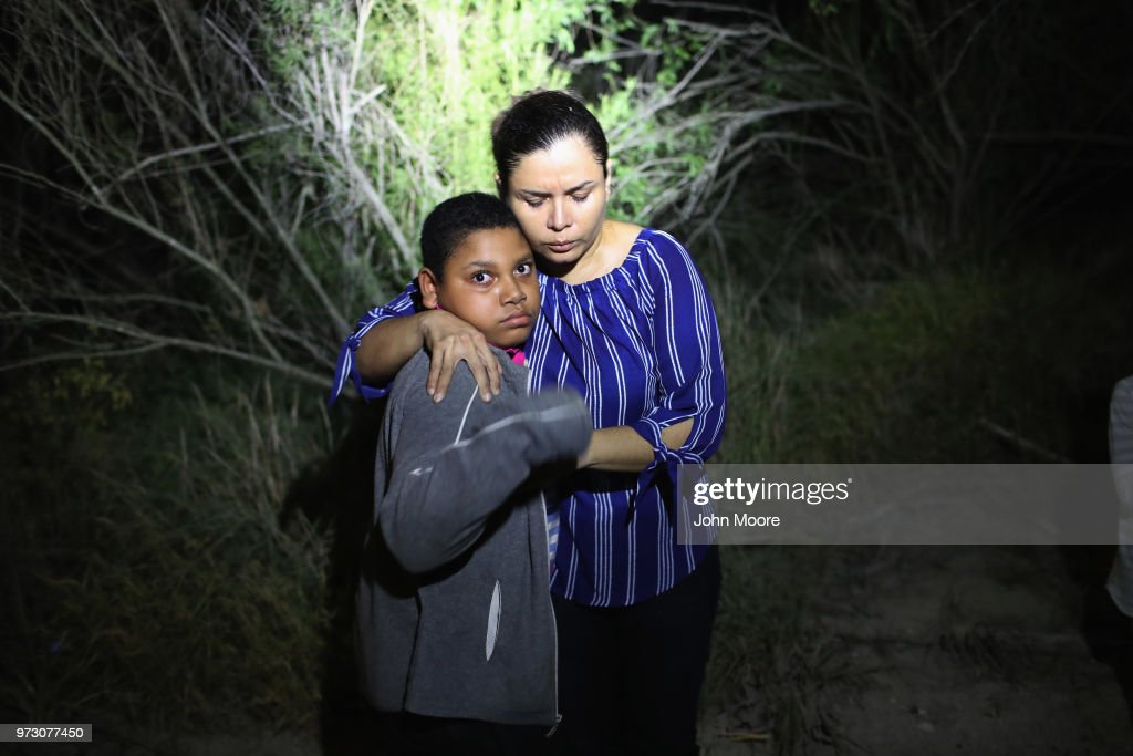 S. Border Patrol spotlight shines on a terrified mother and son from Honduras as they are found in the dark near the U.S.-Mexico border on June 12, 2018 in McAllen, Texas. The asylum seekers had rafted across the Rio Grande from Mexico and had become lost in the woods. They were then detained by Border Patrol agents and then sent to a processing center for possible separation. Customs and Border Protection (CBP) is executing the Trump administration's 'zero tolerance' policy towards undocumented immigrants. U.S. Attorney General Jeff Sessions also said that domestic and gang violence in immigrants' country of origin would no longer qualify them for political asylum status.