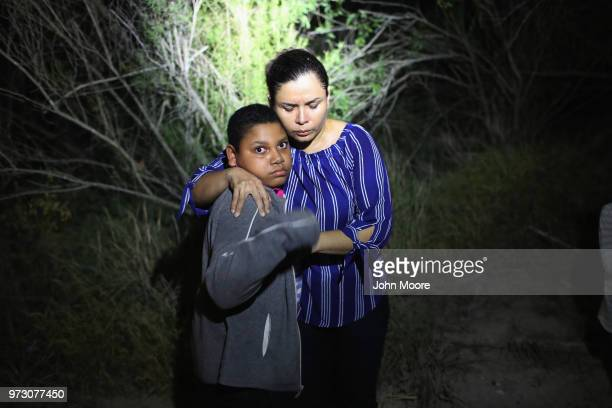 S Border Patrol spotlight shines on a terrified mother and son from Honduras as they are found in the dark near the USMexico border on June 12 2018...