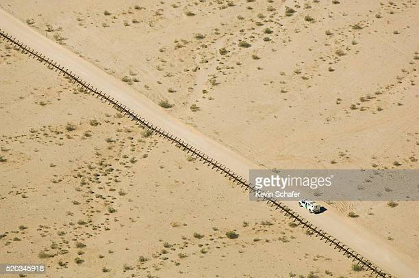US Border Patrol Truck Patroling US-Mexico Border Fence