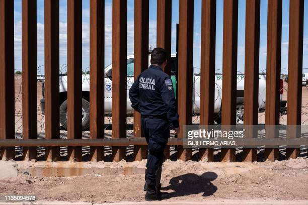 A Border patrol unit and a Mexico's federal police guard near the USMexico border fence as US President Donald Trump visits Calexico California as...