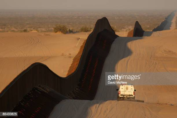 A border patrol vehicle drags the sand to make any new footprints of border crossers more visible along a recently constructed section of the...
