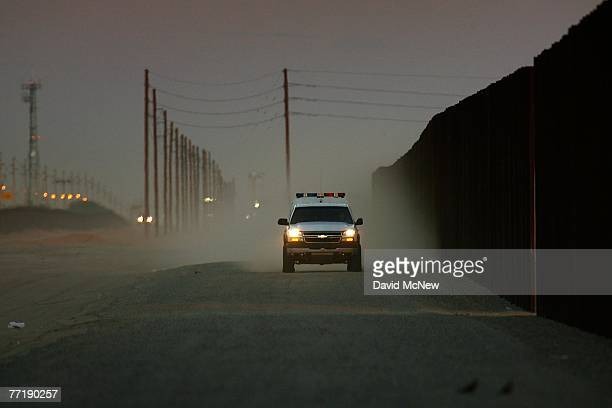 A border patrol vehicle drives along a wall of metal recently constructed by National Guardsmen to form a doublefence border barrier in a dusty...