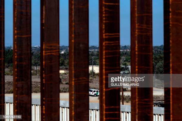 A border patrol vehicle drives as seen through a reinforced section of the USMexico border fence from Tijuana Baja California state Mexico on October...