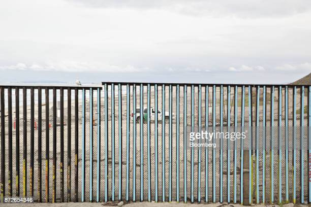 A US Border Patrol vehicle drives on the beach on the American side of a fence standing along the USMexico border as seen from Tijuana Mexico on...