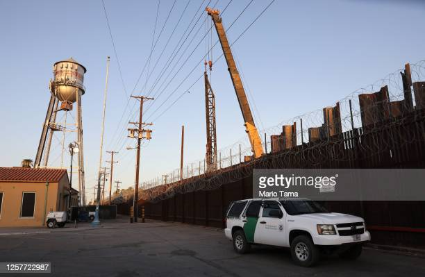 Border Patrol vehicle is stationed in front of the U.S.-Mexico border barrier as construction continues in hard-hit Imperial County on July 22, 2020...