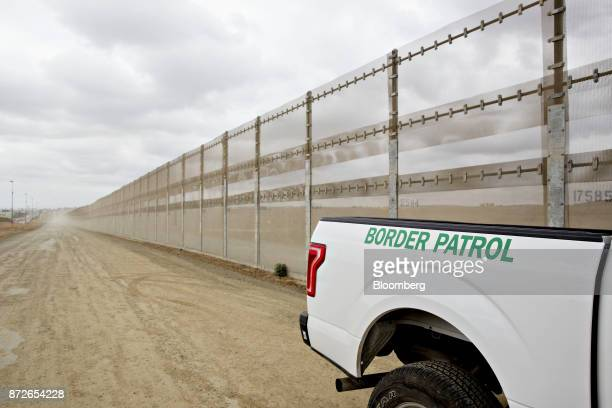 A US Border Patrol vehicle sits parked next to a secondary fence along the USMexico border in San Diego California US on Monday Oct 30 2017 President...